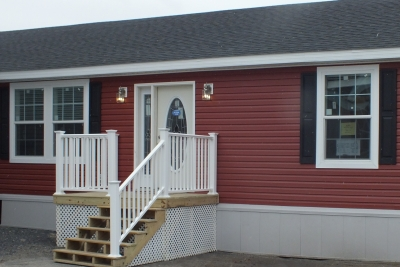 A photo of a red single wide manufactured home