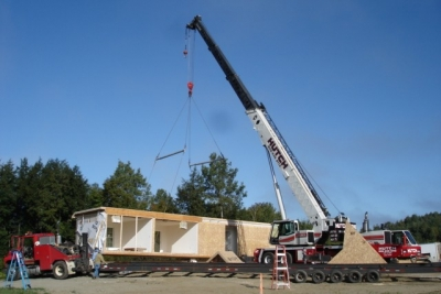 A photo of a construction crane installing a single-wide manufactured home.