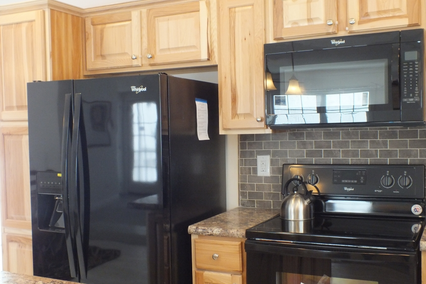 A Photo Of 283 Stock Model Modular Home Black Stove, Refrigerator, And Wooden Cabinets.