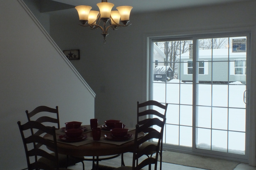 A Photo Of 283 Stock Model Modular Home Dining Area With Table And Large Windows.