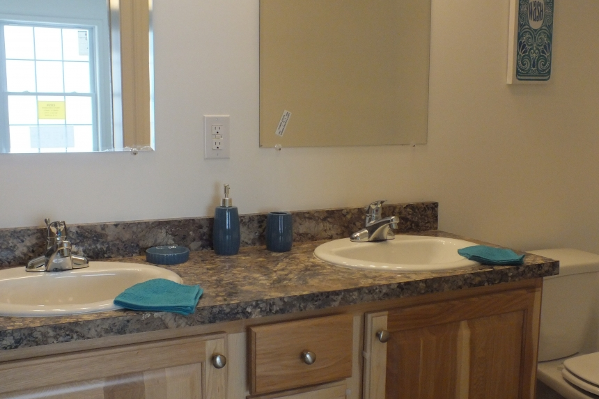 A Photo Of 283 Stock Model Modular Home Twin Bathroom Sinks And Mirror.