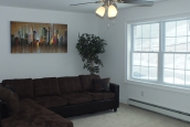 A Photo Of 283 Stock Model Modular Home Furnished Living Area With Couch And Windows.