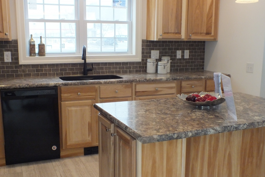 A Photo Of 283 Stock Model Modular Home Kitchen Island, Cabinets, Dishwasher, And Windows.