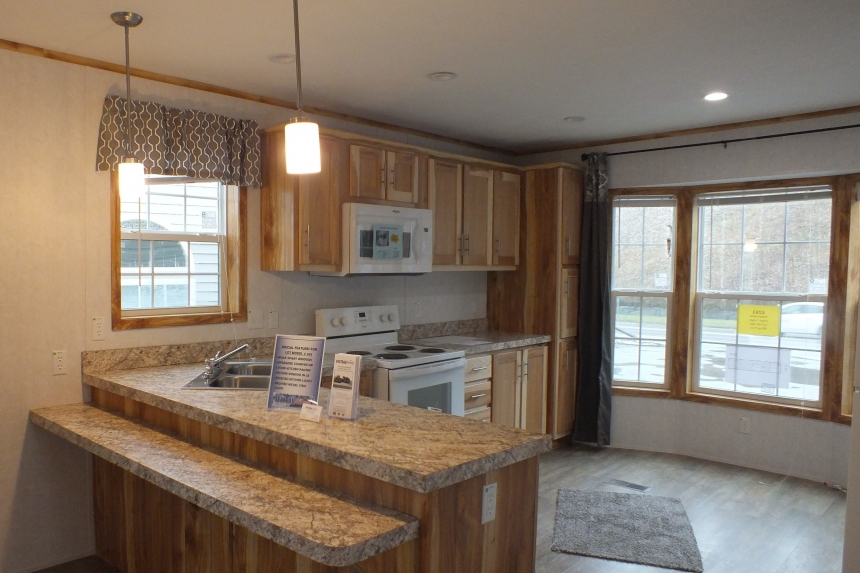 A Photo Of 98 Stock Model Single Wide Home Kitchen With Wood Cabinets And Large Windows