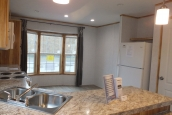 A Photo Of 98 Stock Model Single Wide Home Kitchen With View To Large Windows