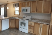 A Photo Of 98 Stock Model Single Wide Home Kitchen Appliances And Wood Cabinets