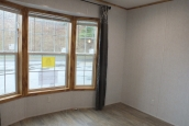 A Photo Of 98 Stock Model Single Wide Home Unfurnished Living Area With Large Windows