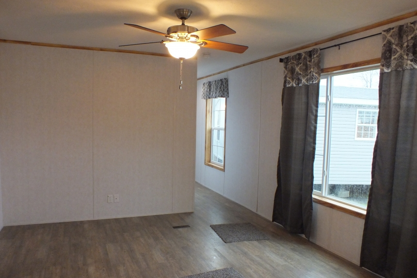 A Photo Of 98 Stock Model Single Wide Home Living Area With Ceiling Fan And Large Windows