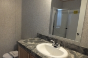 A Photo Of 98 Stock Model Single Wide Home Bathroom Sink With Mirror And Vanity