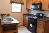Photo Of Single Wide Home 294 Stock Model Kitchen With Black Appliances And Wood Cabinets