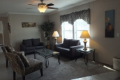 A Photo Of Stock Model 296 Double Wide Home Living Room With Ceiling Fan And Bright Windows
