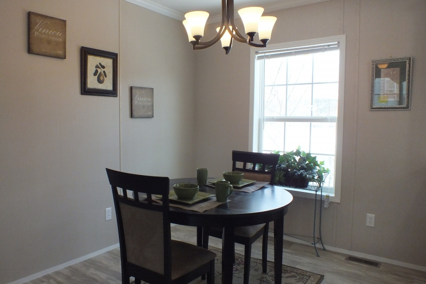A Photo Of Stock Model 296 Double Wide Home Dining Area With Small Table And Bright Window