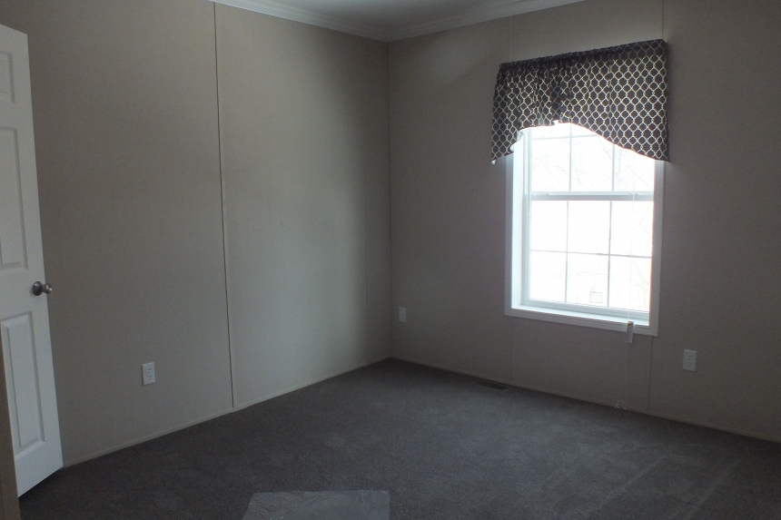 A Photo Of Stock Model 296 Double Wide Home Unfurnished Bedroom With Bright Window