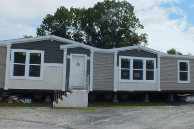 A photo of a beige double-wide manufactured home.