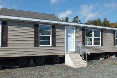 A photo of the exterior of a a three bedroom brown double wide home.