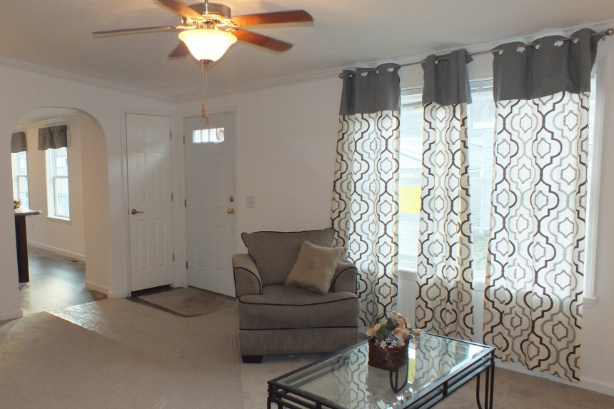 Photo Of Double Wide Home 303 Stock Model Furnished Living Room With Shaded Windows And Ceiling Fan
