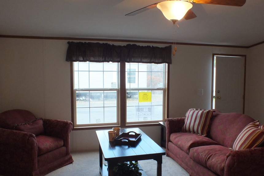 Photo Of Double Wide Home 304 Stock Model Furnished Living Area With Bright Window And Ceiling Fan