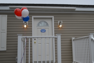 A photo of the front door of a double-wide manufactured home and multicolored balloons.