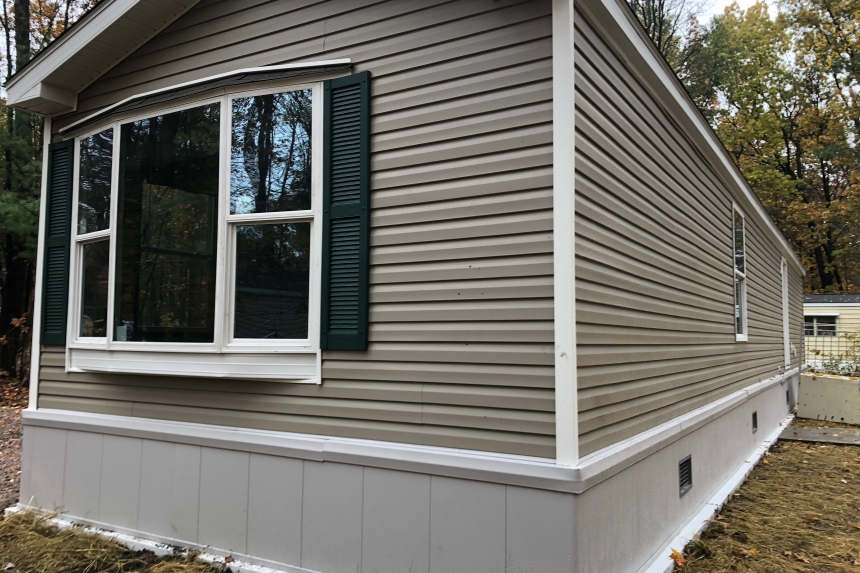 A Photo Of Single Wide Home In Colchester Vermont Tan Exterior Rear With Window
