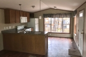 A Photo Of Single Wide Home In Colchester Vermont Kitchen Seen From Living Area With Large Bright Window