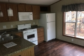 A Photo Of Single Wide Home In Colchester Vermont Kitchen With White Stove Microwave And Refrigerator