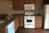 A Photo Of Single Wide Home In Colchester Vermont White Kitchen Stove And Dishwasher With Wood Cabinets