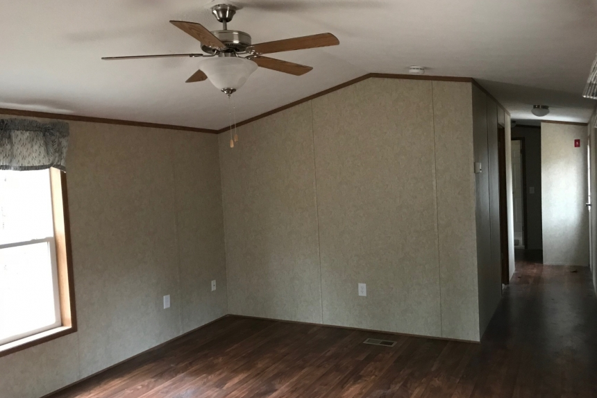 A Photo Of Single Wide Home In Colchester Vermont Unfurnished Living Area With Window And Ceiling Fan