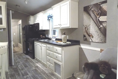 A Photo Of Featured Park Model 355Fl Kitchen With White Cabinets Stove And Refrigerator