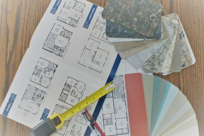 A photo of an home blueprint, color samples, and a measuring tape on a wooden table.