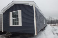 A photo of a blue single-wide manufactured home in Chittenden County Vermont.